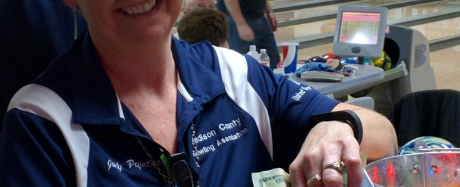 Judy Poynter of the Madison County Bowling Association happily counts funds raised at a recent Lemetta Dause Memorial Tournament.  This year's event is Feb. 4.